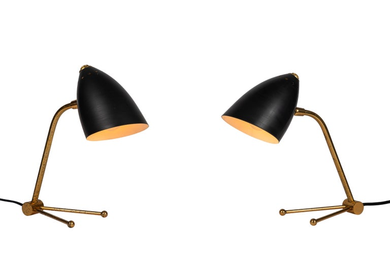 Pair of 1950s Finnish table lamps attributed to Mauri Almari. Executed in black painted metal and patinated brass. Shades rotate up and down and side to side. An incredibly refined design that is quintessentially Finnish.  A contemporary of Paavo