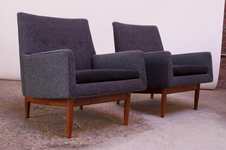 Jens Risom lounge chairs supported by walnut bases, circa 1953. They are relatively small in scale and boast clean, sharp lines. The frame's gray wool upholstery is original, featuring a back button-tufted detail. The cushions have been recovered in