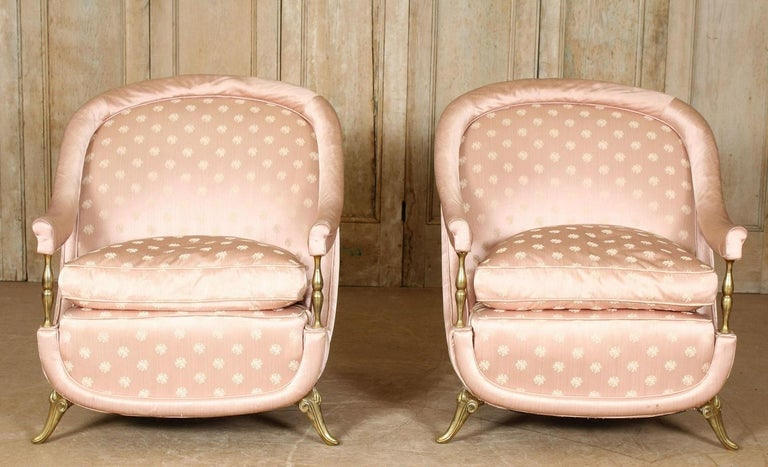 Pair of 1950s French bronze and upholstered lounge chairs. The chairs have satin upholstery, arched backs, sloping arms, loose cushioned seats with bronze feet.