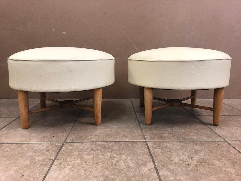 Pair of 1950s, French ottomans. Has a wood X base. Upholstered in leatherette.
