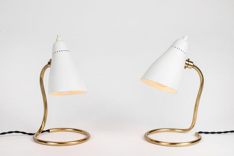 Pair of 1950s Giuseppe Ostuni table lamps for O-Luce. An extremely rare and surprisingly utilitarian pair of lamps executed in white painted aluminum and brass by one of the most refined Italian designers of the midcentury. A highly adaptable light,