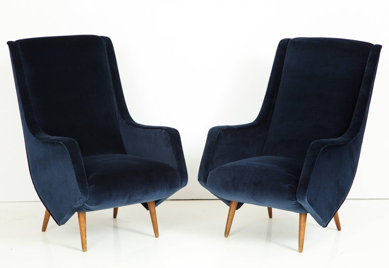 Elegant high pair of vintage Italian lounge chairs attributed to ISA Bergamo with original walnut legs sculptural midcentury Italian design. Completely restored and newly reupholstered in a cobalt blue imported soft velvet. Wooden legs retain their