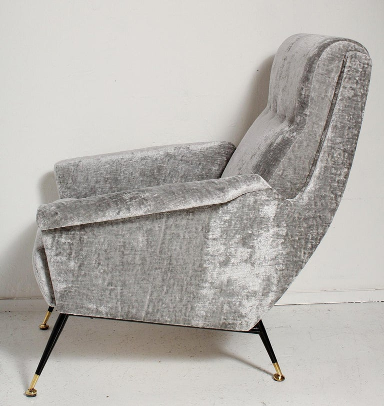 Sexy pair of fully restored 1950s Italian lounge chairs have black metal legs with solid brass sabots, and are upholstered in a luxe, richly textured, grey velvet.