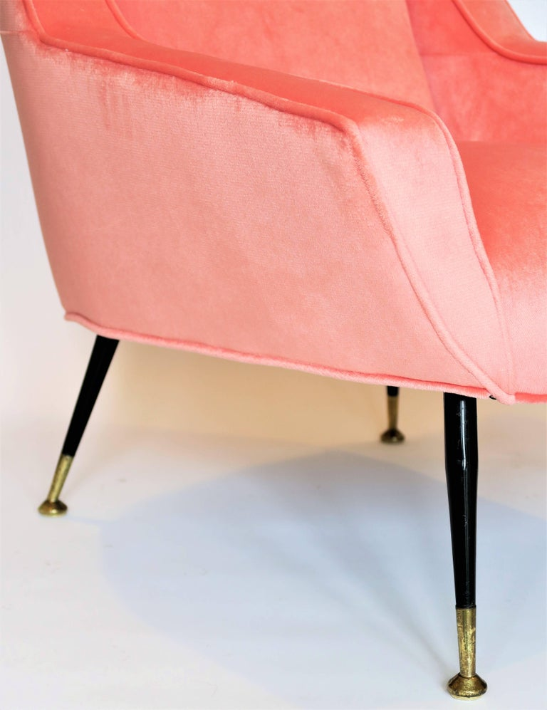 Chic pair of vintage Italian armchairs with black enameled metal and brass feet. Sleek midcentury Italian design with button back. Completely restored and newly reupholstered in a vibrant coral colored imported silk velvet. Legs have been kept with