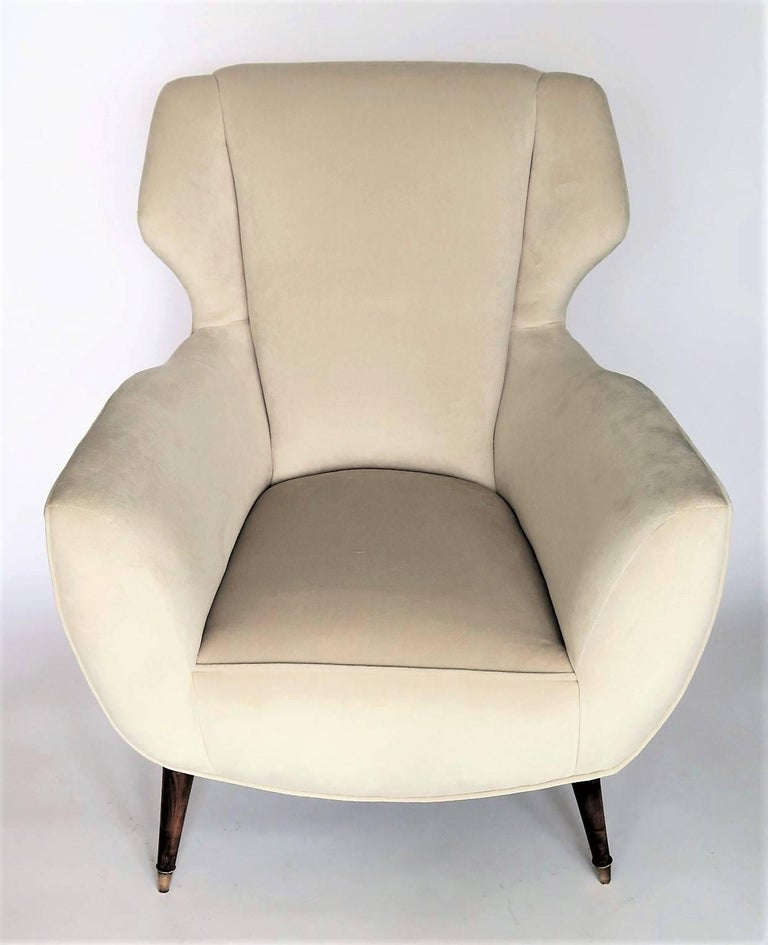 Elegant pair of vintage Italian armchairs with original walnut and brass cap feet. Sculptural mid-century Italian design with winged back. Completely restored and newly reupholstered in a neutral ecru or ivory colored imported soft velvet. Brass