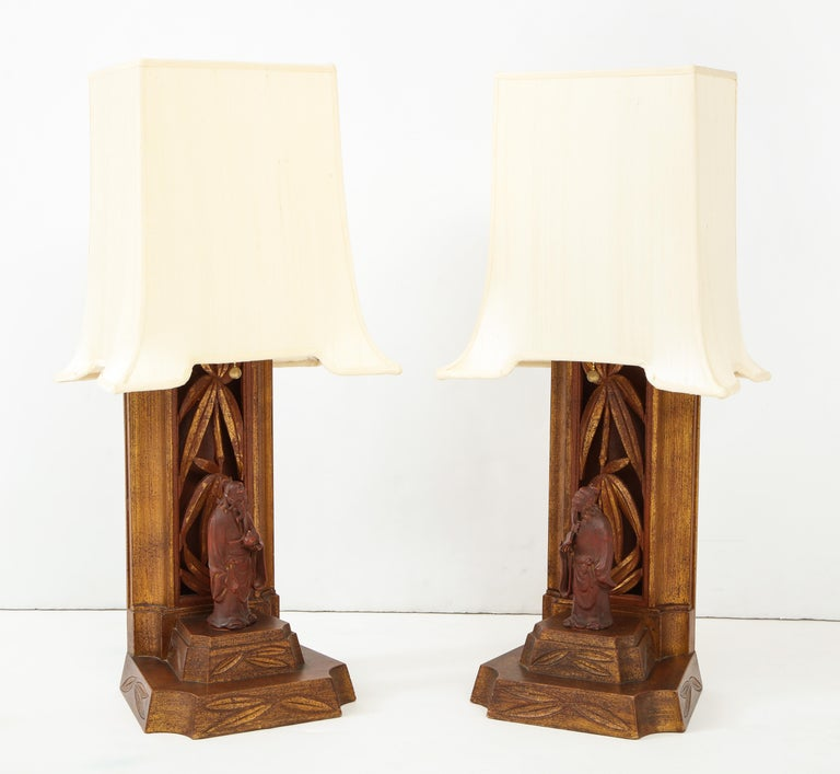 Wonderful pair of 1950s hand carved Chinese figurine lamps by James Mont. The cinnabar lamp bases and figurines are decorated with gold leaf. The lamps have been newly rewired and come with the original pagoda shades which have also been newly