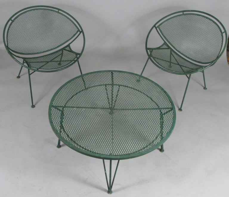 A pair of vintage 1950s wrought iron Radar collection lounge chairs and round companion coffee table designed by Maurizio Tempestini for Salterini. Beautiful design and very comfortable and in their original forest green painted finish. The coffee