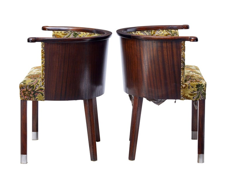 Unusual pair of 1950s tub chairs, circa 1950.  Shaped horseshoe top armrest, with shaped half moon mahogany veneered back.  Standing on block legs, with stainless steel tipped front feet.  Original floral upholstery.  Measures: Seat height: