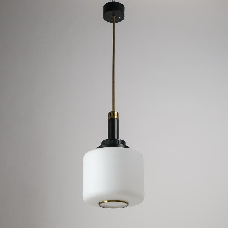 Classic midcentury Italian pendants by Stilux. They have good sized glass diffusers, brass details and tiered and pierced aluminium elements in black. Both are in very good original condition with minimal loss of original paint and a nice patina on