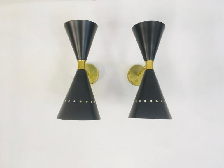 A pair of wall lights Black lacquered metal Brass band and fittings Adjustable 1950s style Made in Italy Price is for a pair Larger quantity can be ordered.