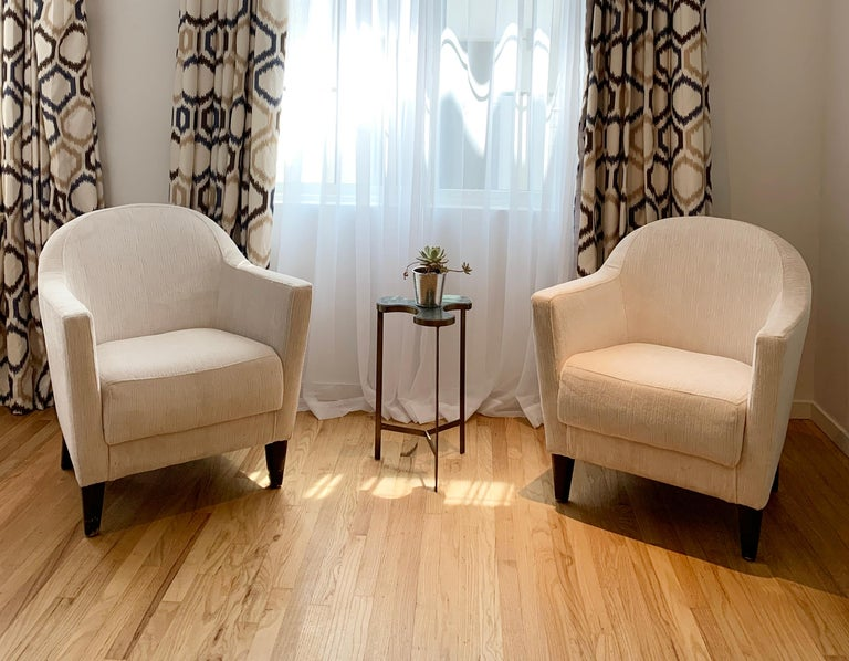 Beautiful pair of 1960s armchairs designed and manufactured in the USA, the chairs have beautiful lines, they are very comfortable and recently upholstered in a beautiful cream chenille fabric. The legs show wear and nicks and scuffs and they can