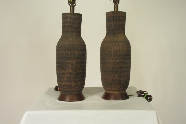 Pair of 1960s ceramic textured table lamps on wood bases.