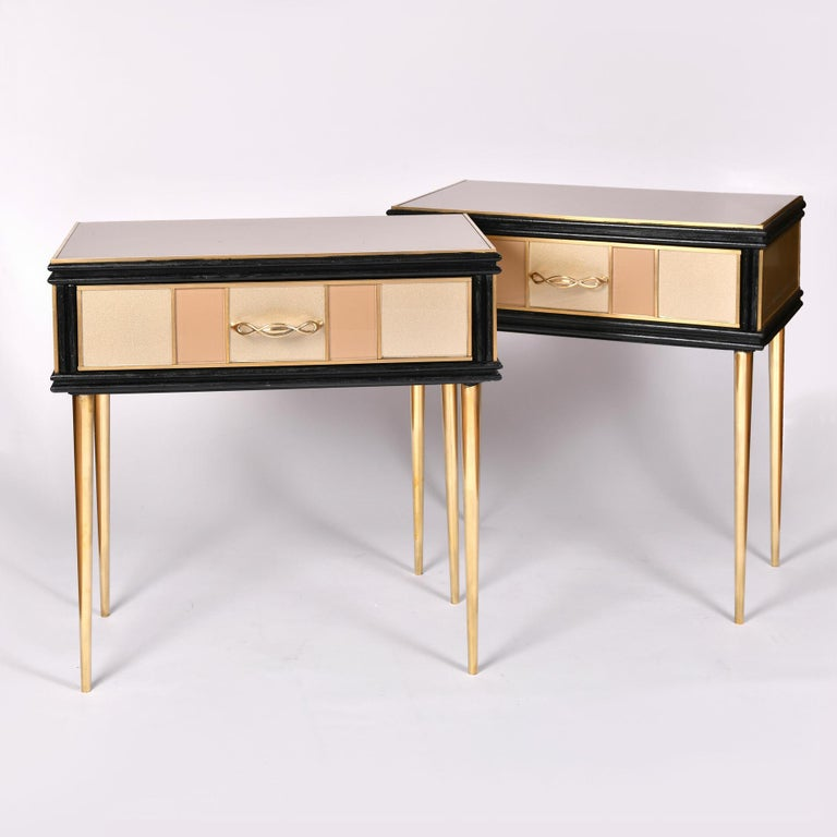 Elegant side tables, each with a single drawer, paneled in alternating gold and cream glass with brass trim and brass twisted handles. 