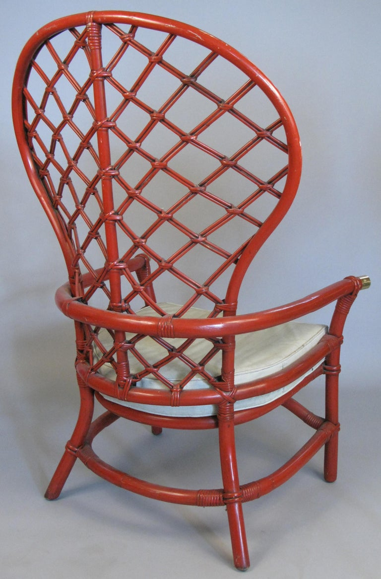 A beautiful pair of vintage 1960s large high back rattan armchairs, with woven lattice design back and brass caps on the armrests. In their original Pompeii red painted finish and vinyl upholstered seat cushions. Great scale and proportions.