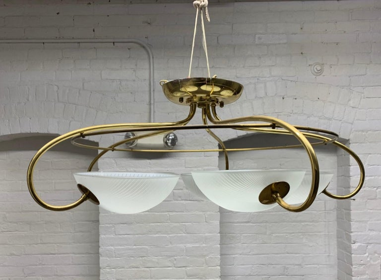 Pair of 1960s, Mid-Century Modern, Italian brass and glass light fixture / chandelier. Has five glass globes with a curved brass structural frame.