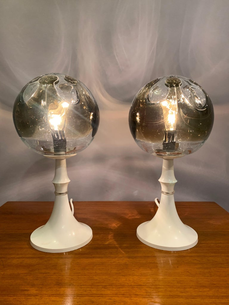 An unusual and rare pair of highly decorative 1960s Kaiser Leuchten table lamps in very good vintage condition. A single hand blown Mazzega clear crystal and smoked glass globe sits on a white plastic formed conical base. Some small signs of age