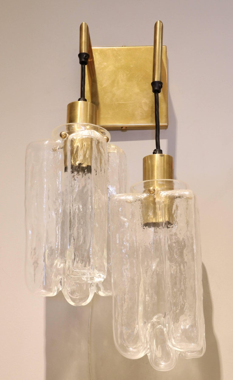 Pair of Kalmar glass sconces from the 1960s with brass wall plate and sockets.