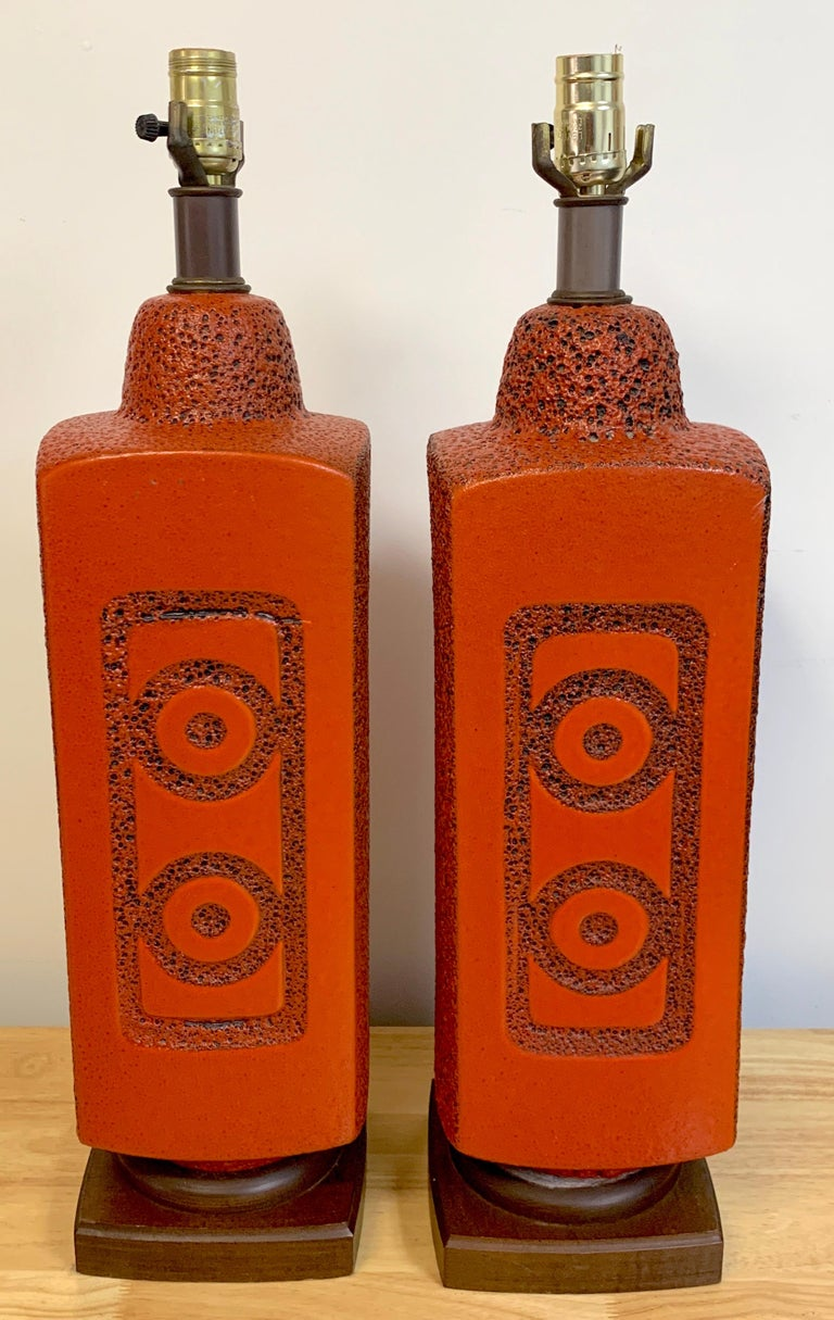 Pair of 1960s mod lava glazed orange lamps, each one with incised roundel and rectangle decoration front and back with rock work sides, raised on 6