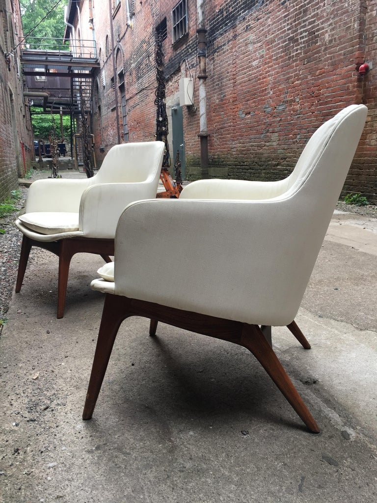 A pair of chairs with amazing lines and profile, circa 1960, The chair backs are upholstered in a white naugahyde/vinyl and the frames are solid Ash construction. Very good original condition.  Measures: 30
