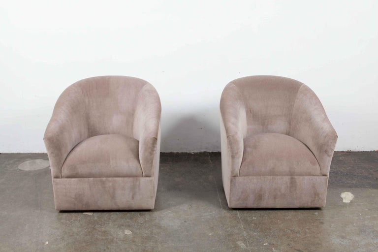 Pair of 1960s American swivel chairs newly upholstered in a grey or brown mohair with a tight back or tight seat upholstery style. Taller, curved back with sloping arms make these an elegant and clean chair that are also quite comfortable.