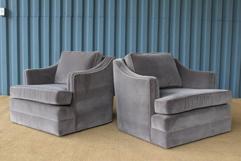 Pair of 1960s club chairs on swivelling bases. New grey mohair upholstery.