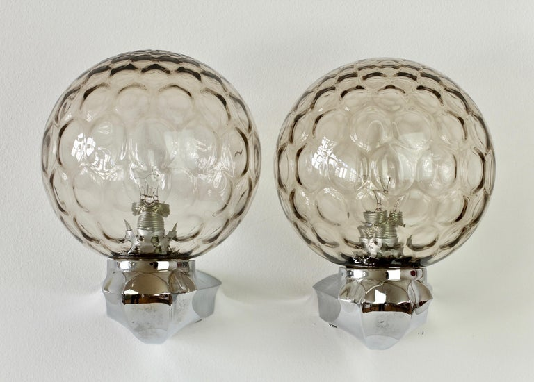 Pair of vintage, German made, Art Deco style wall lights or vanity sconces in the style of Limburg circa 1970s. Featuring dark smoked grey toned / colored (colored) bubble glass globes on chrome-plated metal mounts or brackets in the shape of