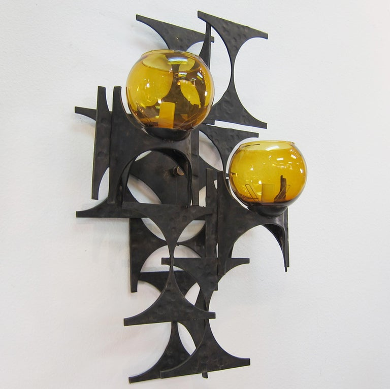 A pair of 1960s steel brutalist sconces with amber glass globes. Very sculptural with a large scale.