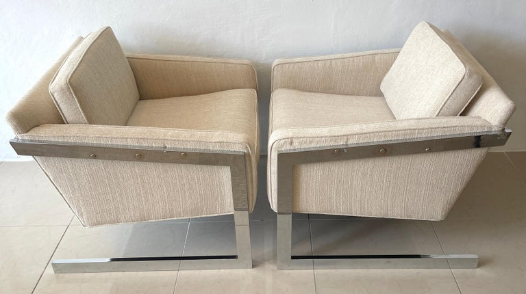 Pair of 1970s chrome cantilever club chairs, newly upholstered, with bright polished chrome frames supporting floating upholstered seats. Very comfortable.  Arm height is 22-Inches Seat height is 17-Inches.