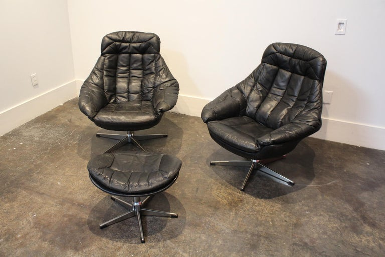 Beautifully-designed, 1970s swivel lounge chairs fully wrapped in black, leather jacket-style leather. In good condition with beautiful wear/light crackling/patina to leather but no major damage or holes. Feet are metal/chrome with very light
