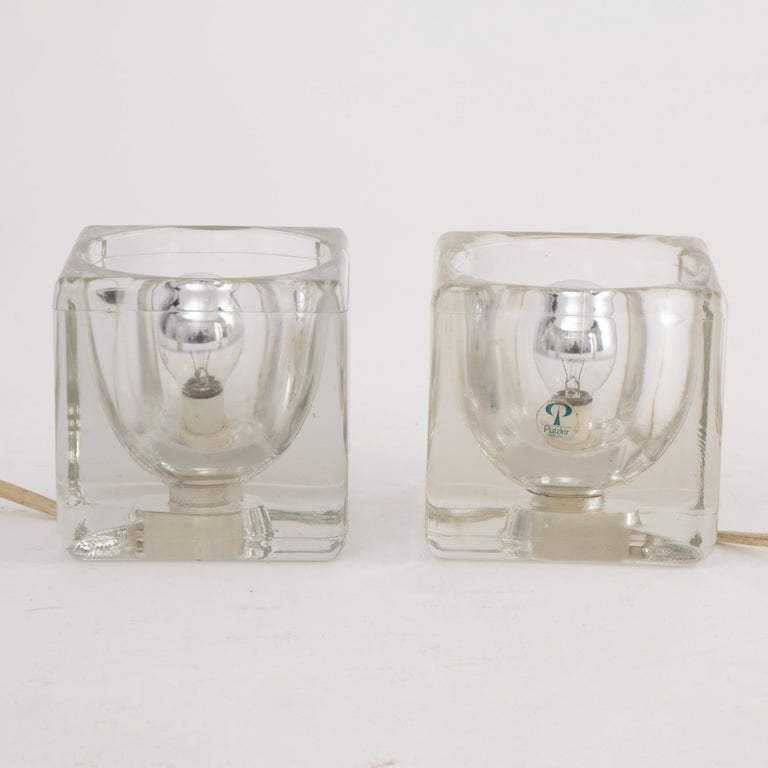Pair of 1970s Peill & Putzler clear glass ice-cube table lamps one with its original label. An on/off switch sits on each original white flex. Perfect for illuminating a dark corner or providing some up lighting. PAT tested and in very good vintage