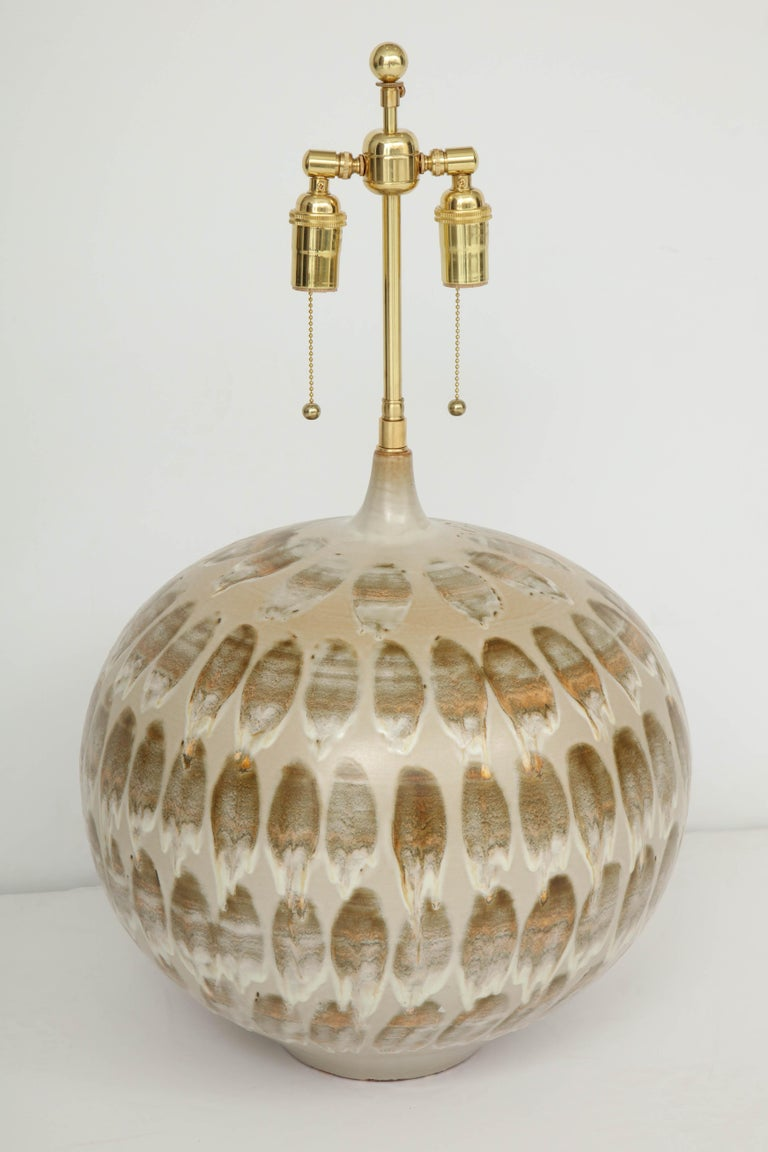 Outstanding pair of giant 1970s ceramic lamps with a wonderful neutral glazed pattern. The lamps have been newly rewired for the US with polished brass double clusters that take standard light bulbs. The height to the top of the ceramic is 17