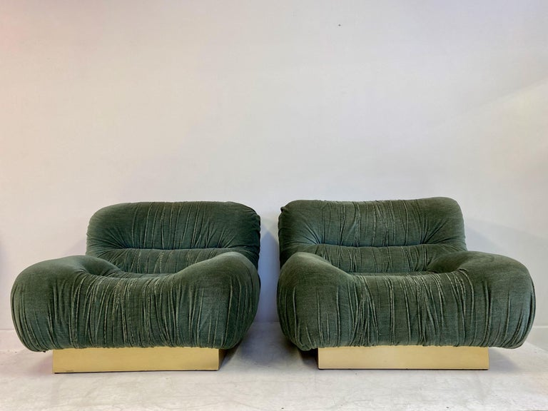A pair of lounge chairs.   Padded velvet.  Brass plinth,  1970s, Italian.   Fabric is a little worn on the ruched edges.   Measures: Seat height 37cm.