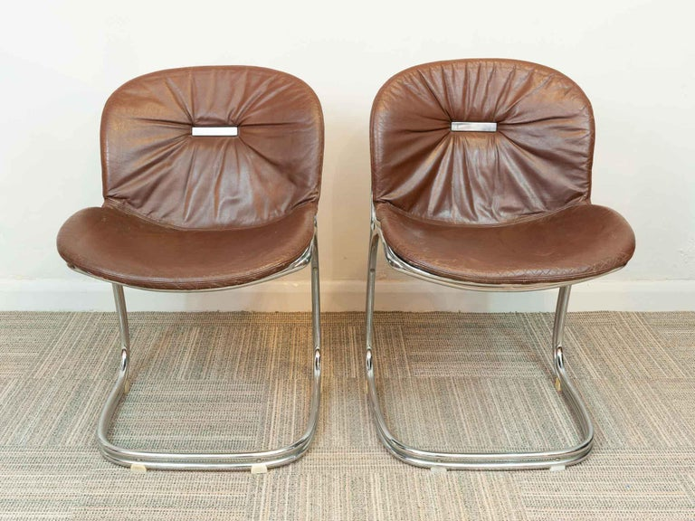 A pair of 1970s Italian cantilevered dining chairs designed by Gastone Rinaldi for Rima in Padova. Model Sabrina. A striking and unusual design featuring a chrome tubular steel cantilevered frame with dark brown leatherette cushions. A feature