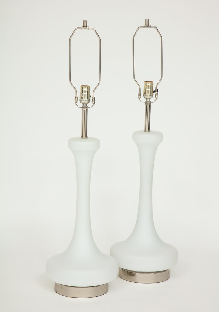 Pair of 1970s midcentury lamps by Laurel Lighting company. The white frosted lamp bodies are mounted on polished chrome bases which can be illuminated by a 3- way switch. They have been newly rewired for the US and take standard light bulbs. The