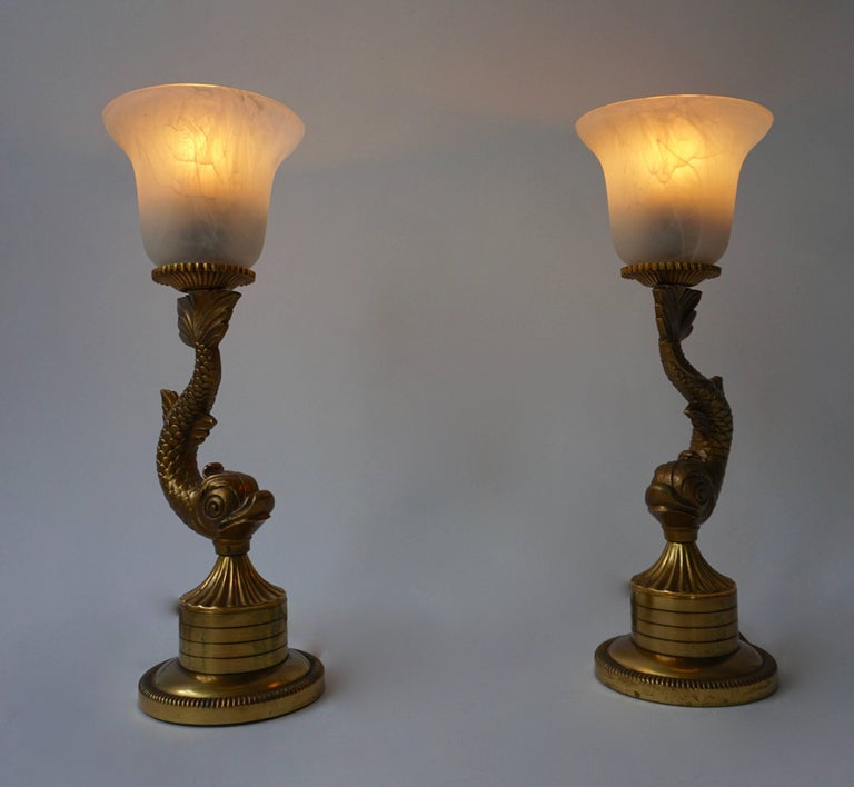 Pair of large 1970s table lamps designed and manufactured in France.   Decorative brass gilt fish design with black glass lampshades.