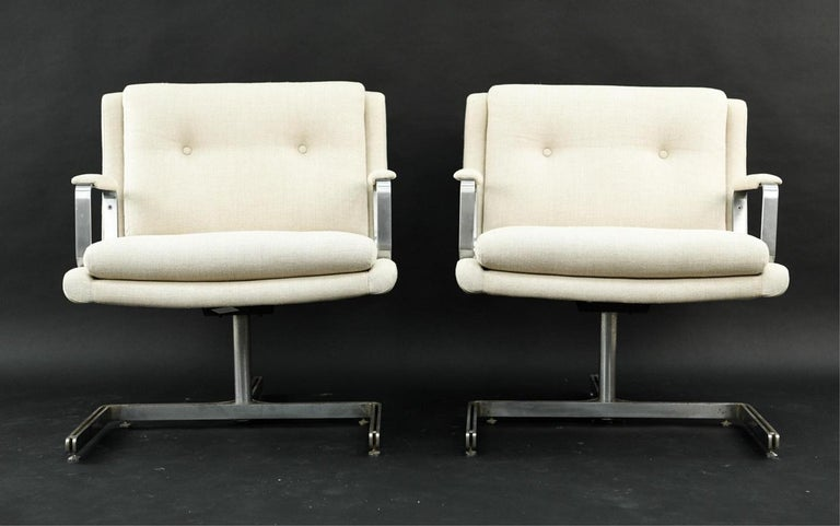 Pair of 1974 Raphael Raffel armchairs. The chairs have an off-white linen blend upholstery with a stainless steel tripod shaped frame.