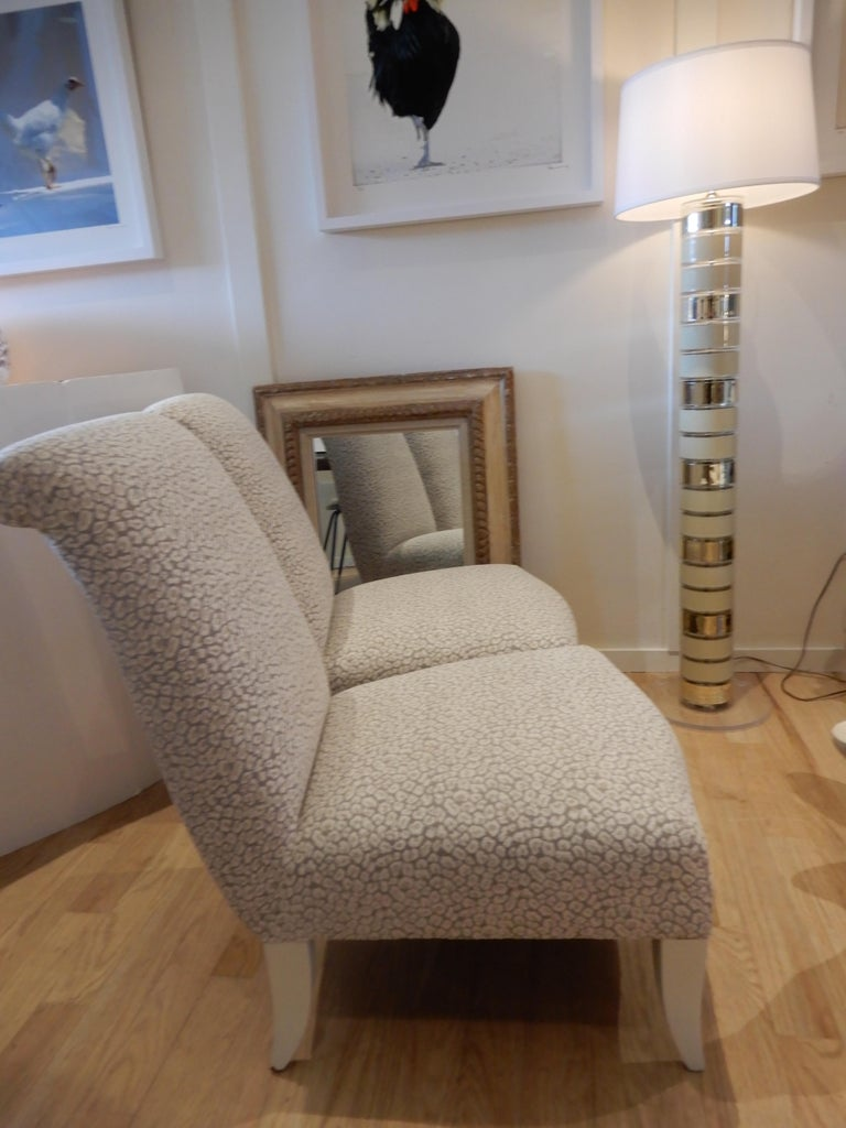 Stunning pair of newly upholstered Donghia slipper chairs/side chairs, in a Clarence house animal print luxurious fabric. Rolled head rest, painted legs in a bone beige.Priced for the pair.