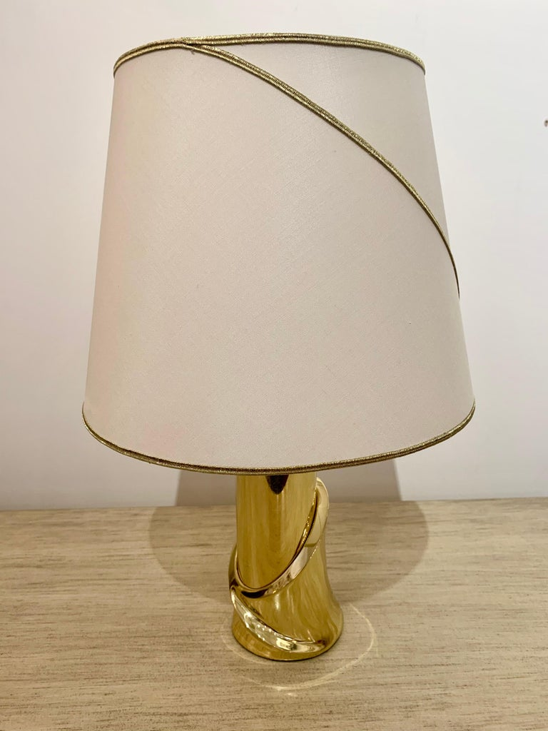 A pair of luxurious 1980s sculptural polished bronze table lamps with the original matching shades. The shades have been newly recovered and the gold piping matches the swooping lines design of the bases. Newly rewired. Made by coveted Italian