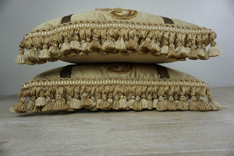 Pair of custom pillows designed by Melissa Levinson with 19th century metallic appliques on silk fronts. Silk damask backs and tassel trim at sides of pillows. Down inserts, sewn closed.