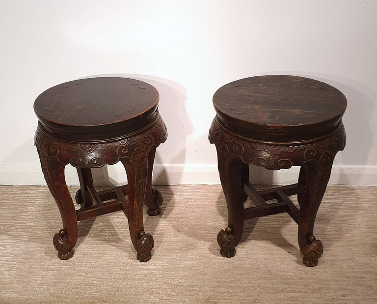 This lovely and decorative pair of 19th century Chinese hardwood stands feature a circular top and supported on 4 ornately carved cabriole legs joined together with a squared stretcher at the base. Each one measures 15 1/2 in - 39.4 cm in diameter