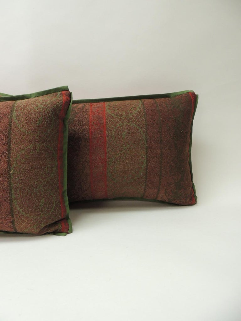 Pair of 19th century antique woven Kashmir decorative pillows with green flat cotton trim and red carriage cloth fabric backing.