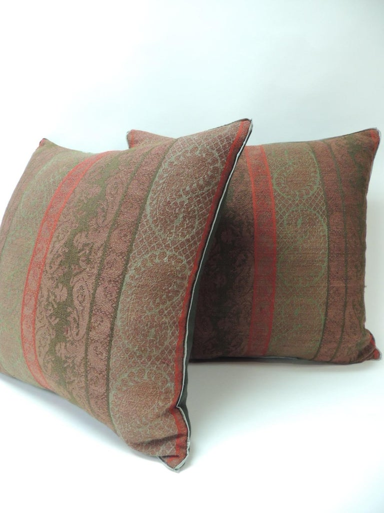 Pair of 19th century antique woven red and green Kashmir decorative pillows with green flat green silk trim and hunter green carriage cloth fabric backing.