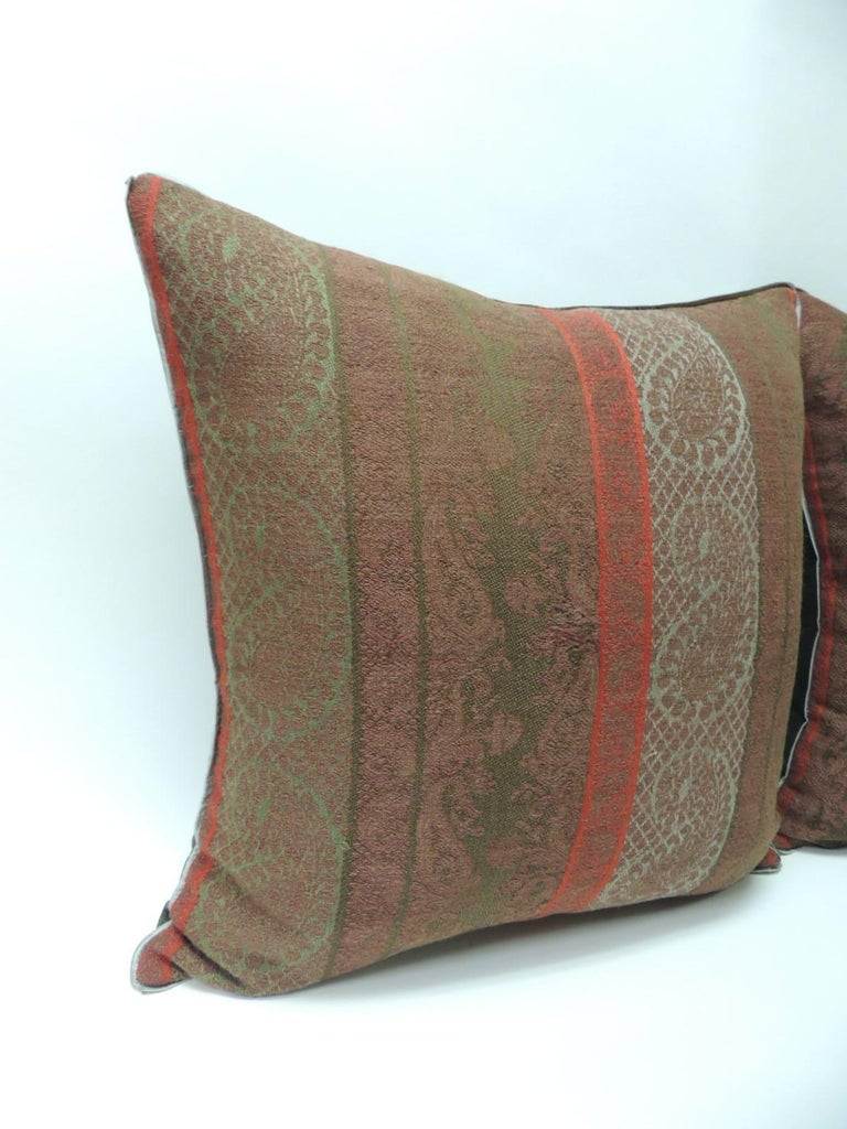 Pair of 19th century antique woven red and green Kashmir decorative pillows with green flat green silk Trim and hunter green carriage cloth fabric backing. In shades of brown, green, red and soft green. Handcrafted decorative pillow made with an