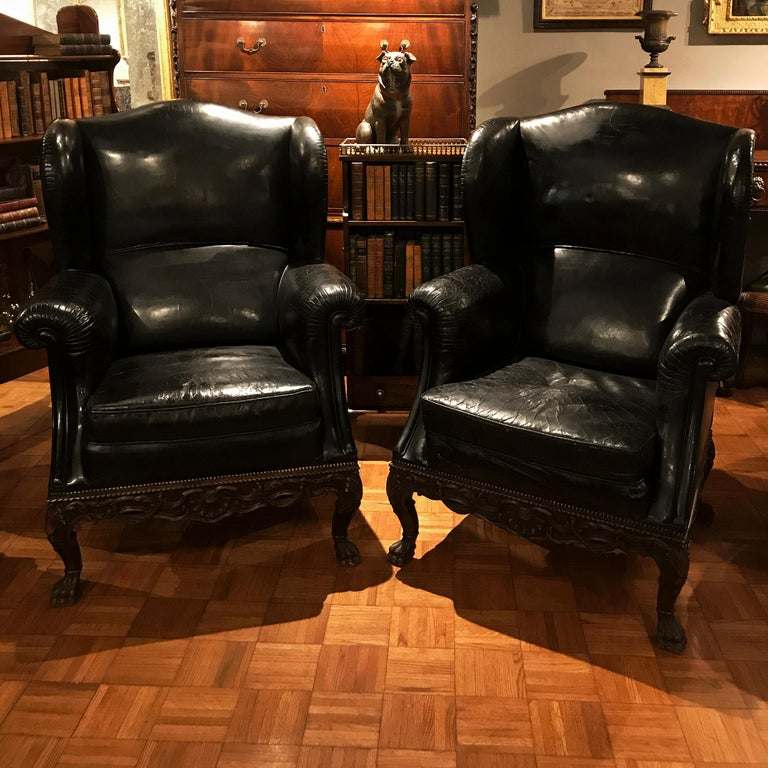 This pair of 19th-century black leather armchairs is distinguished by the Georgian-style shell and acanthus carving on the apron and cabriole legs of each chair, ending in stylized lion's paw feet. Each of these highly comfortable and generously