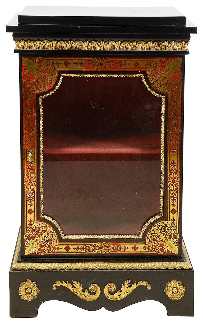 A good quality pair of French 19th century Boulle side cabinets, having ebonized tops and sides, gilded ormolu mounts, glazed doors to each with red velvet interior and shelf. Classical motif brass inlaid decoration to the red stains tortoiseshell,