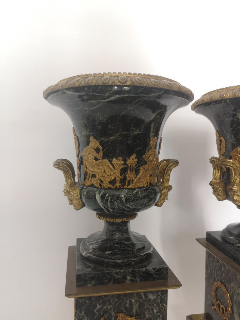 A pair of 19th century gilt bronze and green marble urns, decorated with classical gilt bronze mounts. French, circa 1880.