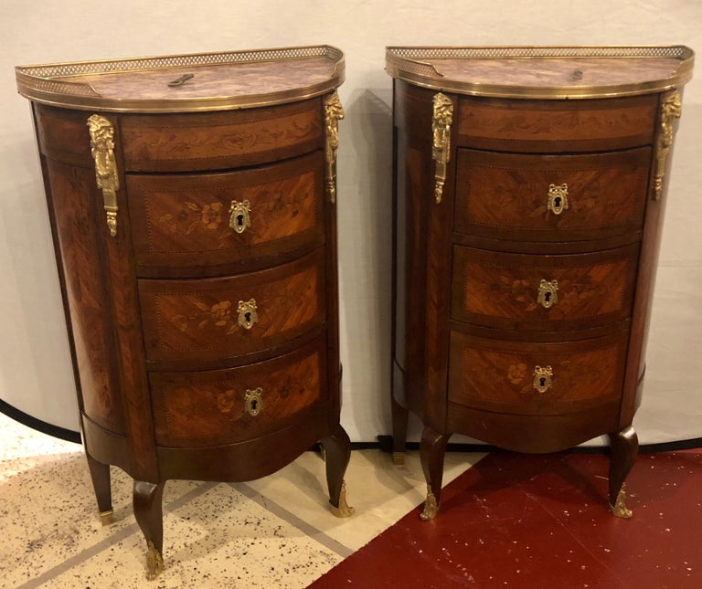 A pair of 19th century bronze mounted demilune end tables or nightstands. Fine demilune form with bronze galleried marble tops on floral inlaid fronts. 1 drawer missing an interior lock.  hxax.