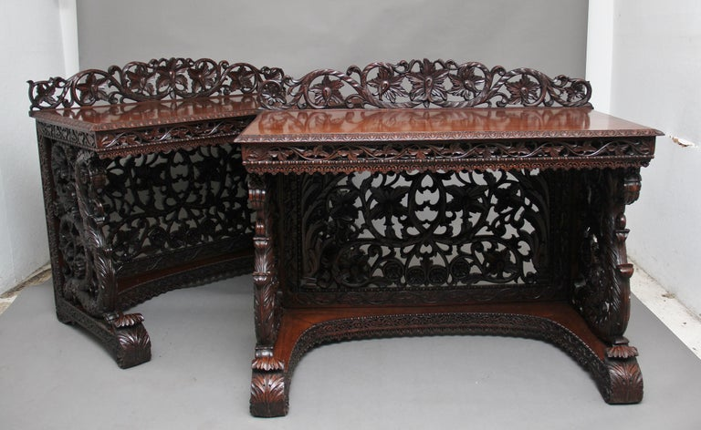 A superb pair of 19th century Indian carved console tables, each having a foliate scroll-carved pierced back over a rectangular top with ovolu-moulded edge upon pierced foliate scroll frieze, scroll apron and well carved conforming sides and back,