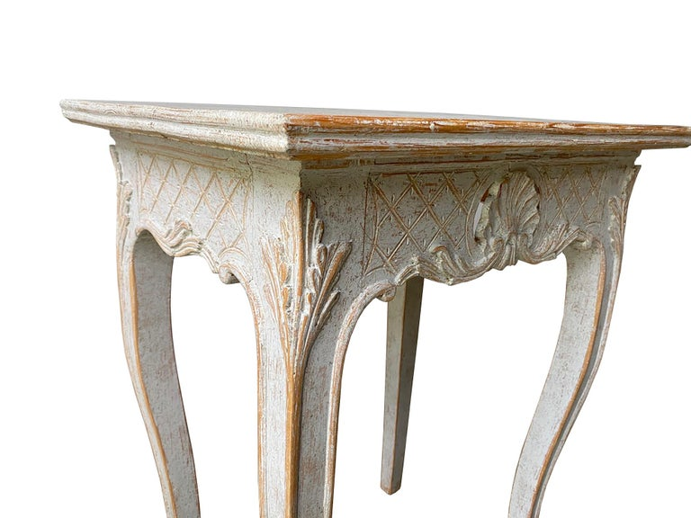 This decorative pair of 19th century tables feature a carved decorative freeze with diamond and shell design, and cabriolet legs with acanthus leaf decoration.