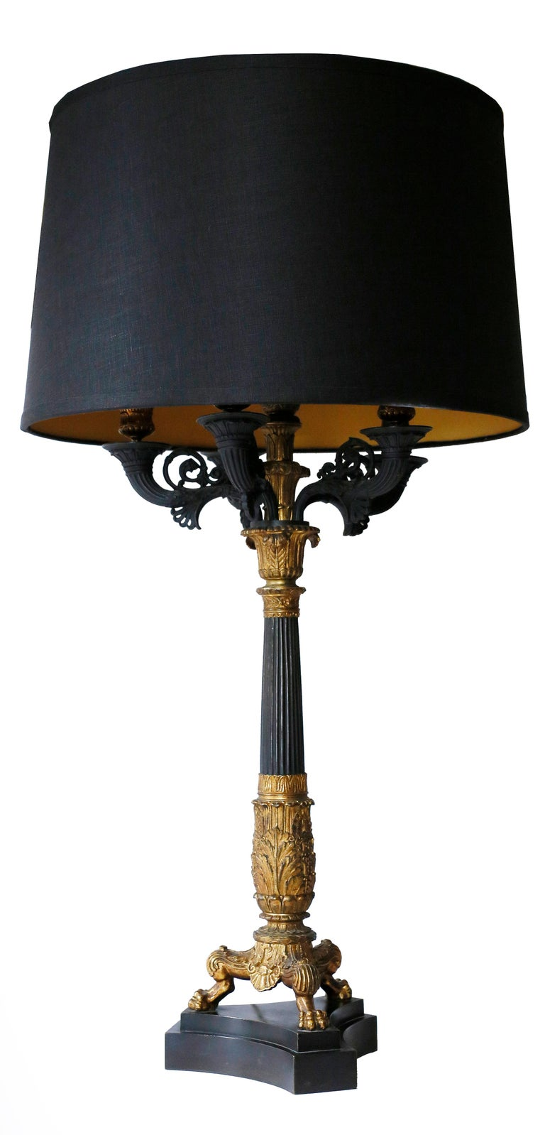 A fine pair of baluster neoclassical lamps of patinated bronze with gold detailing. A black basalt stone base supports a paw-footed tripod with a baluster detailed with fluting and acanthus. The five light candle supports exhibit scrolls and bronze